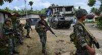 Philippine marines walk next to their V-300 light wheeled armoured vehicle after engaging Islamist militants at in Marawi, on the southern island of Mindanao on June 2, 2017./AFP