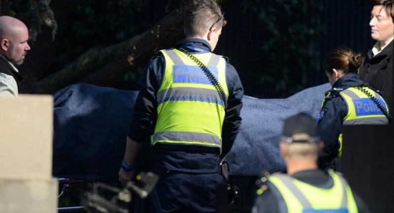 Police officers help the coroner remove a body at the scene of a hostage situation in the Melbourne bayside suburb of Brighton Tuesday./AFP