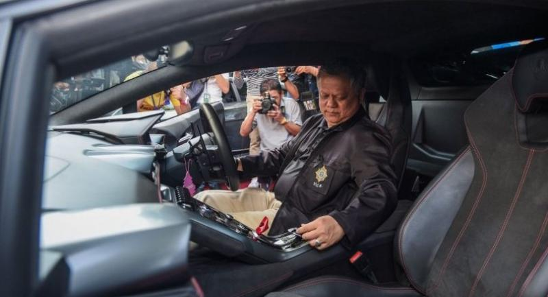 An official from the Office of the Narcotics Control Board (ONCB) has his hand on a Lamborghini luxury car put under the hammer during yesterday's auction by the anti-drugs agency at its office.