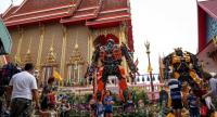 This photo taken on June 18, 2017 shows people enjoying giant metal statues inspired by the Transformers franchise, by Ban Hun Lek metalworks, at Wat Tha Kien Buddhist temple in Nonthaburi./AFP
