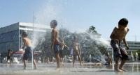 Children play with water-jets to cool off at the fountain on the Place des Nations, during a heatwave, in Geneva, Switzerland, 20 June 2017. // EPA PHOTO