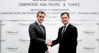 Dean Schreiber, left, managing director of Oakwood Asia Pacific, shakes hands with Prinya Tienworn, chairman of VMPC, at yesterday's signing ceremony for Oakwood Hotel