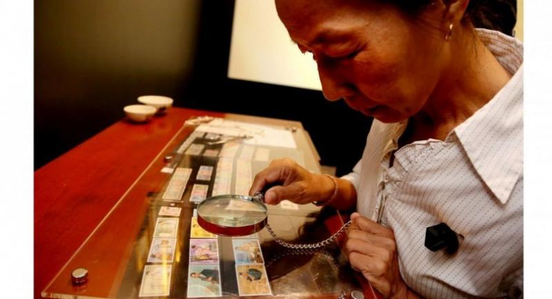 A woman uses a magnifying glass to admire stamps related to HM the late King Bhumibol Adulyadej at the Grand Postal Building in Bangkok's Bang Rak district yesterday.