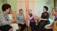 This photo taken and released on June 30 shows the wife of China's President Xi Jinping, Peng Liyuan (2nd R), chatting to residents during her visit to an elderly care facility in Hong Kong.//AFP