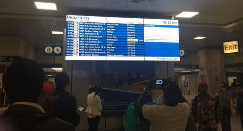 Passengers look at an board displaying delayed trains at the Penn Station in New York on July 6, 2017, following a train derailment. A New Jersey transit train derailed at Penn Station halting service to the terminal. // AFP PHOTO