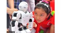 A school girl gazes at a robot on display at an expo in Zhengzhou, Henan province, May 27, 2017. [Photo/VCG]