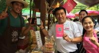 Government Savings Bank president Chatchai Payuhanaveechai, centre, buys products at a retail shop at Amphawa district, Samut Songkharmprovince, using the QR Code payment at the shop.