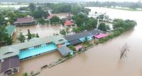A canal overflows in Phitsanulok province yesterday, flooding Ban Pluak Ngarm School. With floodwaters at least one metre deep, the school suspended classes and asked nearby residents for help to move teaching materials to higher ground.