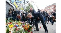 Hamburg's mayor Olaf Scholz lays down flowers at a makeshift memorial of flowers and candles on July 29, 2017 in front of a supermarket in Hamburg, northern Germany. / AFP PHOTO