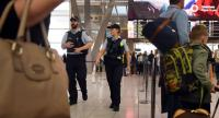 Police walk past passengers as they patrol Sydney Airport on July 30, 2017. /AFP