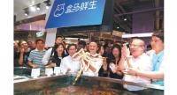 Jack Ma, founder and chairman of Alibaba Group Holding Ltd, picks up an imported crab in the newly opened Hema Xiansheng outlet in the Jinqiao area of Shanghai on July 14.