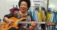 This picture taken on August 5, 2017 shows Mary Ho, also known as Grandma Mary, posing with her electric guitar during a rehearsal in Singapore. // AFP PHOTO