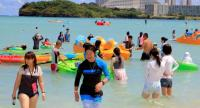 Tourists enjoy the activities along Tumon beach on the island of Guam on August 11, 2017. /AFP
