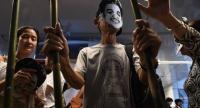 This file photo taken on June 22, 2017 shows activists standing behind makeshift bars wearing masks of Thai human rights activist Jatupat Boonpattararaksa. /AFP
