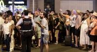Tourists wait for the police to allow them to come back to their hotel on the Rambla boulevard after a van ploughed into the crowd, killing at least 13 people and injuring around 100 others is towed away from the Rambla in Barcelona./AFP