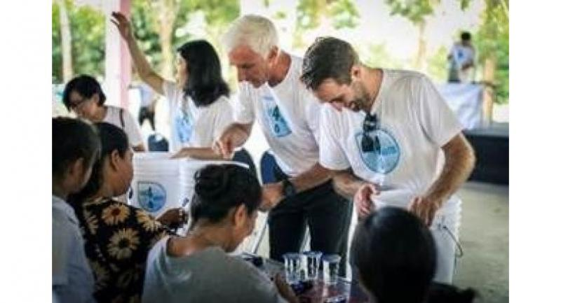 Jeffrey Gaudiano, left, president and CEO, BMW Group Manufacturing Thailand, demonstrates the use of water filter system to the locals.
