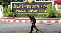 An official sweeps the road in front of the Bangkok Remand Prison Saturday morning.