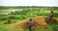 Border Guard Bangladesh (BGB) personnel stand alert as Rohingya people (far L) escape fresh gunfire at the Bangladesh-Myanmar frontier near Rakhine on August 26.//AFP