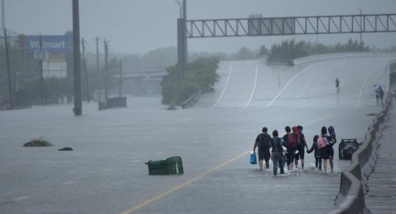 Evacuation residents from the Meyerland area walk onto an I-610 overpass for further help during the aftermath of Hurricane Harvey August 27, 2017 in Houston, Texas. // AFP PHOTO
