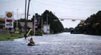 A woman paddles down a flooded road while shuttling deliveries for her neighbors during the aftermath of Hurricane Harvey on August 30, 2017 in Houston, Texas./AFP