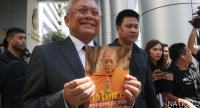 Former deputy prime minister Suthep Thaugsuban happily shows a dhamma book after he heard the Supreme Court's ruling Thursday morning.