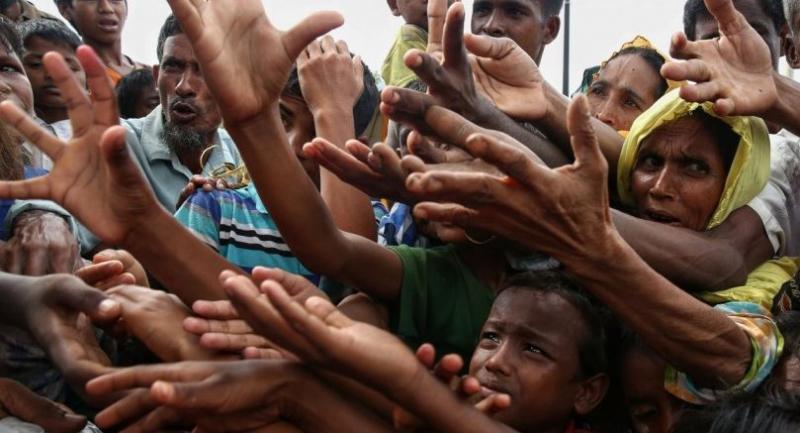 This photo shows Rohingya refugees reaching for food aid at Kutupalong refugee camp in Ukhiya near the Bangladesh-Myanmar border.//AFP
