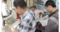 People read the final edition of the Cambodia Daily on Monday. The Tax Department yesterday filed criminal complaints against the paper's founder and two of its directors. Tang Chhin Sothy/AFP