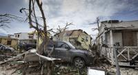 This handout photograph provided courtesy of the Dutch Department of Defense on September 7, 2017 shows houses and cars damaged after the passage of Hurricane Irma on the Dutch Caribbean island of Sint Maarten. // AFP PHOTO