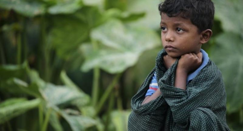 A Rohingya boy sits on a wall near a newly build refugee camp on a small hill in Ukhiya, Cox's Bazar, Bangladesh on September 11.//EPA-EFE