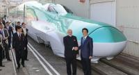 This file photo taken on November 12, 2016 shows India's Prime Minister Narendra Modi (2nd R) and his Japanese counterpart Shinzo Abe (R) shaking hands in front of a Shinkansen train during their inspection of a bullet train manufacturing plant./AFP