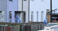 Investigators are pictured outside a house during a police raid in Sunbury, Surrey near London on September 16, 2017. // AFP PHOTO