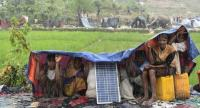 Rohingya refugees protect themself from the rain in Bangladesh's Balukhali refugee camp on September 17.//AFP