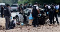 Thai forensic officers inspect an area near the crater caused by bomb blast that wrecked the pickup in Pattani province yesterday. Four soldiers were killed and six others injured.