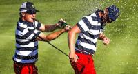 US team member Charley Hoffman (L) sprays down US team member Daniel Berger (R) after Berger completed his match against International team member Si Woo Kim of South Korea.