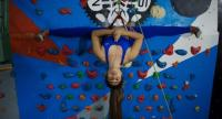 Khin Myat Thu Zar, a 32-year-old former lawyer who has been teaching yoga in Myanmar professionally for the last five years, performs a yoga pose on a climbing wall during a class at a studio in Yangon in August.//AFP