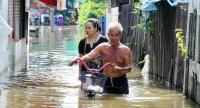 Residents of the Wat Bang Luang community in Pathum Thani's Sam Khok district yesterday wade through floodwaters that have persisted for about a week. The situation is worsening as the Chao Phraya River is rising due to runoff.