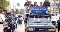 Khunying Sudarat Keyuraphan on a pickup truck equipped with a banner of her name during a marigold-|planting activity in tribute to the late King.