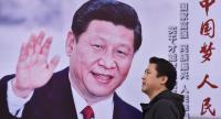 A man walks past a poster featuring Chinese President Xi Jinping with a slogan reading