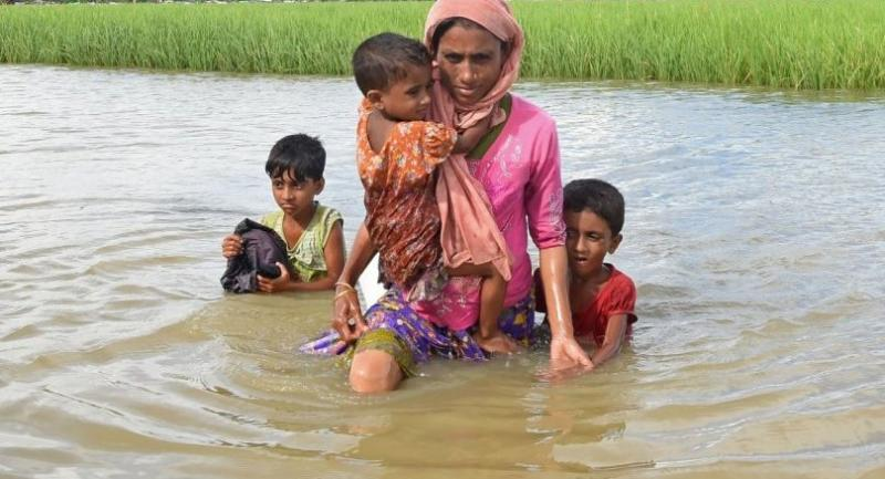 Rohingya refugee Khalida, a mother of three children, wade across a canal near the no man's land area between Bangladesh and Myanmar in the Palongkhali area next to Ukhia on October 18, 2017./AFP