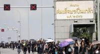 Mourners in black attire walk across Pinklao Bridge to attend the Royal Cremation ceremonies at Sanam Luang yesterday.