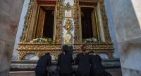 Mourners prostrate before Phra Ubosot, or ordination hall, of Wat Bovoranives where the Buddha statue Phra Buddha Chinnasi is located, under which the second portion of the late King's ashes will be laid.