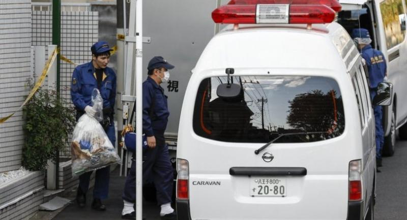 Police investigators and crime lab experts bring out plastic bag as they investigate an apartment house (L) in Zama, Kanagawa Prefecture, Japan on October 31.//EPA-EFE