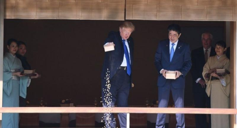 US President Donald Trump (C) feeds koi fish as Japanese Prime Minister Shinzo Abe (R)looks on during a welcoming ceremony in Tokyo on November 6, 2017. // AFP PHOTO