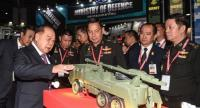 Deputy Prime Minister and Defence Minister General Prawit Wongsuwan inspects a model of an armoured vehicle during the Thailand Defence and Security 2017 event in Bangkok yesterday.
