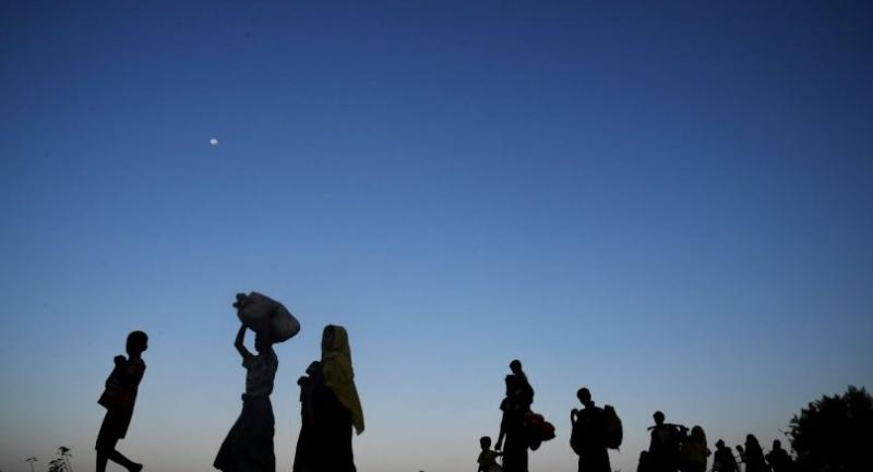 Rohingya Muslim refugees who were entered Bangladesh by boat walk towards refugee camps after landing in the Bangladeshi district of Teknaf on November 7, 2017./AFP