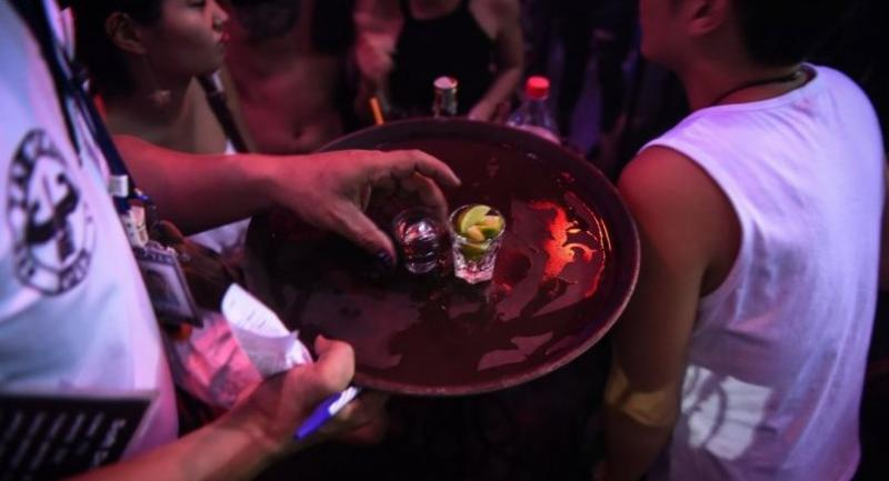 This photograph taken on October 7, 2017 shows a waiter serving alcohol to a group of Chinese tourists at ZAG bar in Thailand's southern tourist destination of Phuket. /AFP