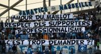 Olympique de Marseille (OM) fans hold a banner reading