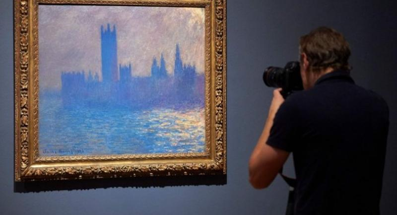 "A photographer takes a picture of the Houses of Parliament by French artist Claude Monet at the exhibition ""French Artists in Exile"" (18701904) at Tate Britain in London. /AFP"