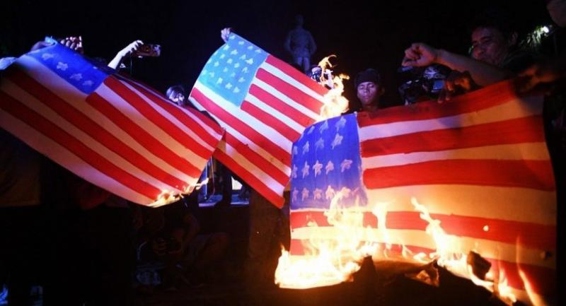 Protestors burn US flags during a vigil during a protest against visiting US President Donald Trump before the start of the 31st Association of Southeast Asian Nations (ASEAN) Summit in Manila on November 12, 2017. / AFP PHOTO