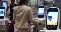 A passenger scans her thumb at an automated immigration gate at the newly-opened Changi International Airport Terminal 4 in Singapore./ AFP PHOTO